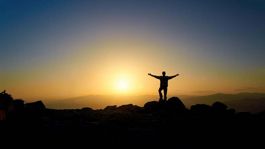 Image of a man feeling liberated after climbing a mountain. I had a similar feeling after conquering one recent experience through emotional release.